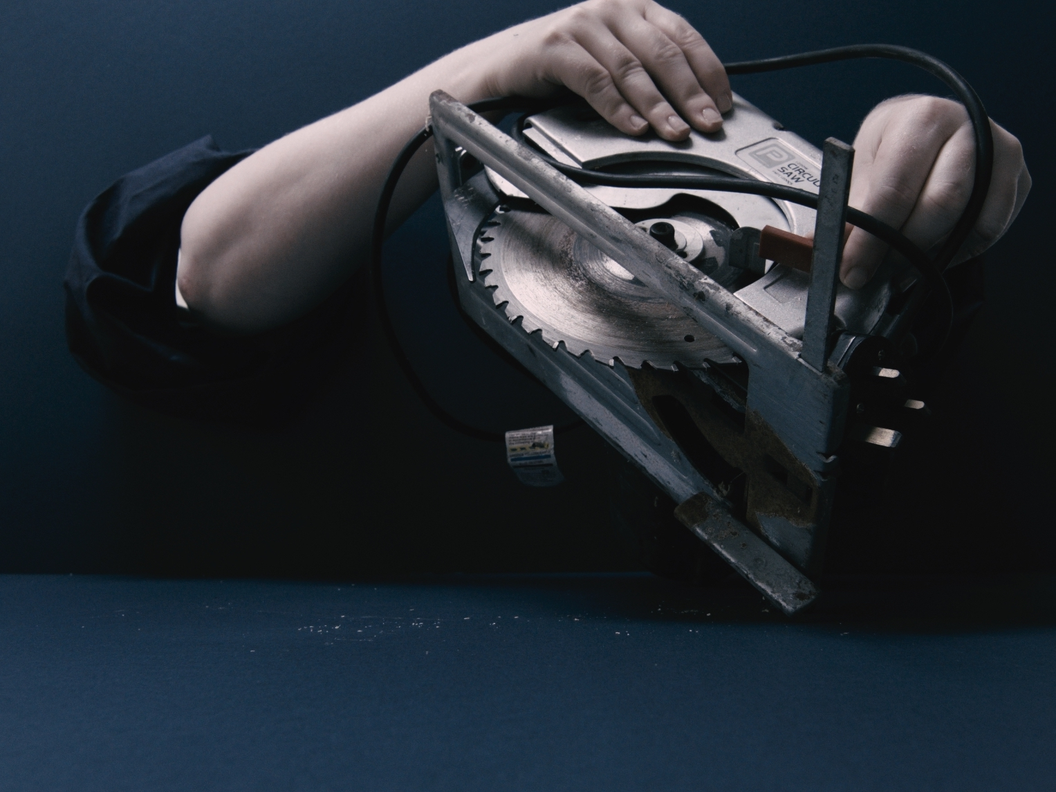 A pair of white arms poke through holes inside a dark blue box. They touch the object inside; a round, metal, circular saw, with it's teeth bared